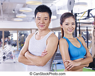young couple in gym - young asian couple standing back to...