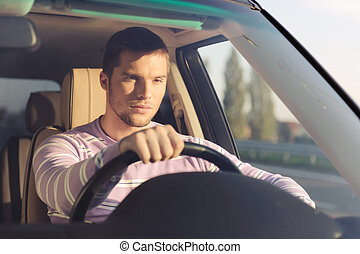 Taking a long drive - Handsome young man driving a car...