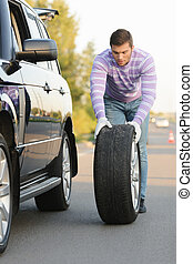 Young man rolling a spare wheel - Handsome young man rolling...