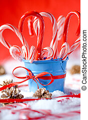 Peppermint canes christmas background - Blue bucket full of...