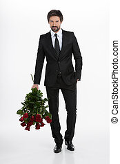 Men with bunch of roses. Handsome young businessman holding a bunch of red roses and standing against white background