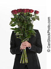 Hiding behind the roses. Young man holding a bunch of red...