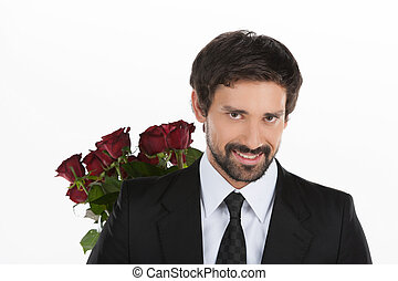 Handsome with roses. Handsome young businessman holding a bunch of red roses behind his back and standing against white background