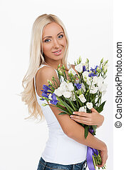 Beautiful women with flowers. Attractive young woman holding a bunch of flowers and smiling while standing against white background