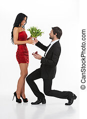 I love you! Young man in full suit standing on one knee and giving a bunch of flowers to his girlfriend while isolated on white