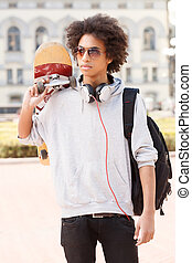 Teenager. African descent teenager holding skate and looking...