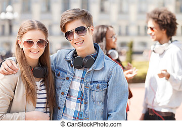 Teenage friends. Two cheerful teenage friends standing close to each other and smiling at camera while their friends talking on the background
