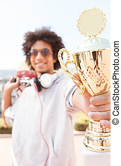 Teenager Cheerful African descent teenager showing trophy...
