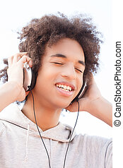 Teenager listening to the music. Cheerful African descent...