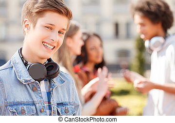 Teenage friends. Cheerful teenage boy smiling at camera while his friends talking on the background