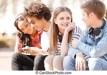 Teenage friends Four cheerful teenage friends talking to...