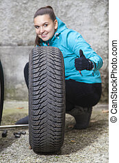 Pretty girl replacing car tyre