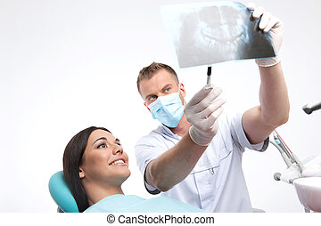 Patient at dentist office. Beautiful young woman sitting at the chair in dental office while doctor showing something at X-ray photo