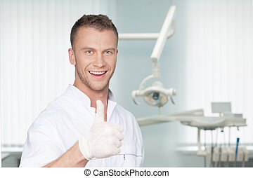 Cheerful dentist. Smiling young dentist in protective gloves looking at camera and gesturing