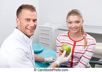 Patient at dentist office. Dentist and patient looking at camera and smiling while doctor holding apple