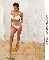 Female in her underwear stepping on a scale - Photo of a...