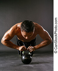 Pushups with kettlebell - Photo of a muscular Asian man...