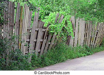 Wooden Fence - An old worn wooden fence falling over and in...
