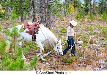 Trail Riding - Beautiful brunette cowgirl with her horse on...