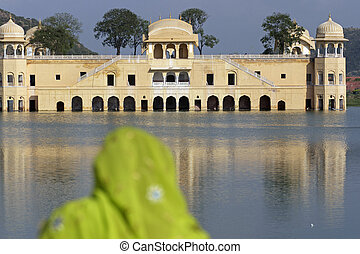 Jal Mahal in Jaipur - Indian lady in colorful sari looking...
