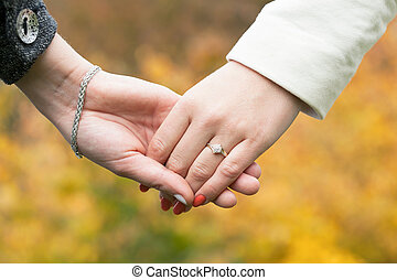 Two women holding hands during walking in park