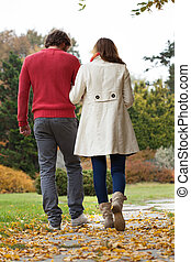 Autumn path - Young man and woman walking down autumn path
