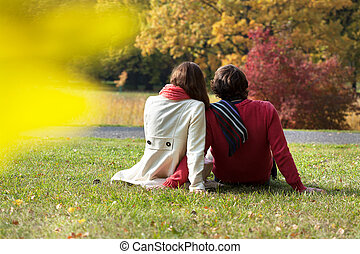 Sunny day - Student's couple sitting in park during sunny...