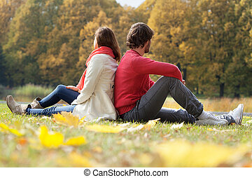 Dreaming about future - Young couple sitting in autumn park...