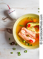Salmon soup with chive and chili pepper