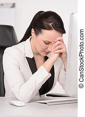 Bad day at office. Depressed middle-aged businesswoman sitting at her working place with her eyes closed and holding the head in hands