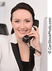 How can I help you? Confident middle-aged businesswoman sitting at her working place talking at phone