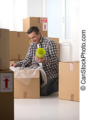 House moving Cheerful middle-aged man packing the cardboard...