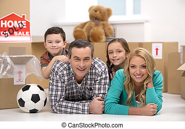 Happy family. Cheerful family lying together near the cardboard boxes and smiling