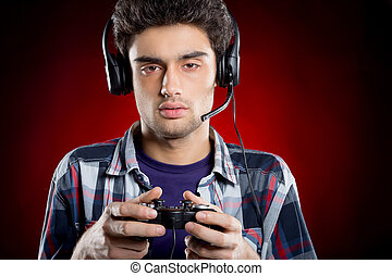 Tired gamer. Teenage boy playing video games and looking...