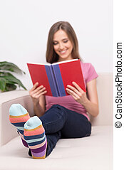 Woman reading book. Beautiful young woman reading book while lying on the couch