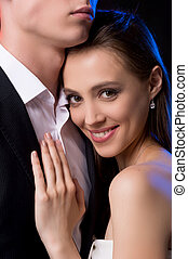 Loving couple. Beautiful young woman leaning to her boyfriend and smiling