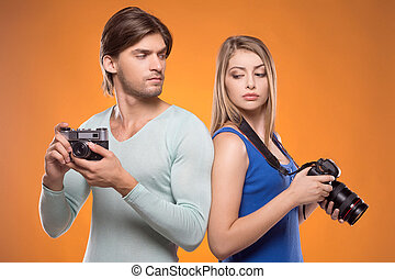 Photographers. Two photographers holding cameras in their hands and looking at each other while standing isolated on coloured background