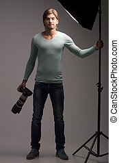 Man with camera. Full length of confident young man holding camera in his hands and looking at you