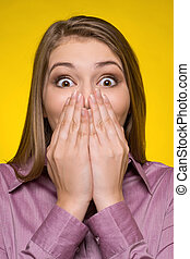 Shocked woman. Surprised young woman covering mouth with hands and looking at camera while isolated on yellow