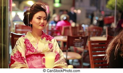 Japanese geisha at cafe - Japanese geisha sitting at cafe at...