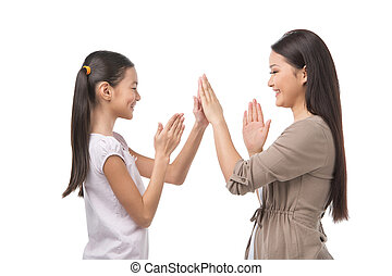 Mother and daughter. Cheerful mother and daughter playing together while isolated on white