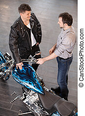 Examining motorcycle Cheerful young sales executive...