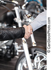 Good deal. Close-up of handshaking with a motorcycle on the...
