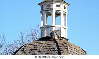 Man sitting at the roof of bell tower fixing the roof of the...