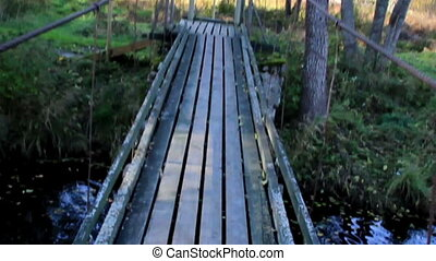 Walking on wooden bridge while water flowing under it