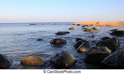 Water near the seashore is constantly moving on the rocks