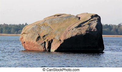 Big rock in the middle of the sea and near the shore you can...