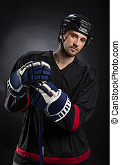 Attractive young hockey player posing on camera. Standing...