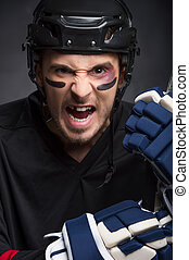 Portrait of hockey player with screaming angry look. Without...