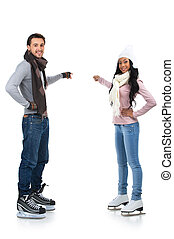 Smiling couple skating together. Pointing with finger on background